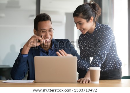 Millennial indian female employee explain issue to laughing african American male colleague, cooperating together at laptop, smiling multiethnic diverse coworkers talk discuss project using computer
