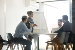 Millennial indian female speaker stand making flip chart presentation speak on company business strategy, diverse multiethnic work team brainstorm discuss share ideas meeting at briefing in office