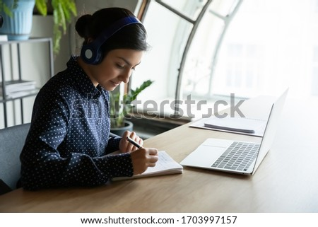 Millennial Indian girl in wireless headset study watch webinar make notes at home, young ethnic woman in earphones have online consultation or video call on laptop, webcam conference with colleagues