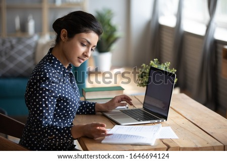 Millennial Indian girl sit at desk in living room study on laptop making notes, concentrated young woman work on computer write in notebook, take online course or training at home, education concept