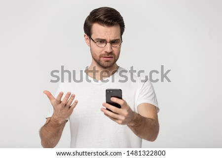 Millennial mad man annoyed by slow internet, received spam message, broken phone, troubles with shopping app, connection to wifi, looking at screen, isolated on grey white studio background.