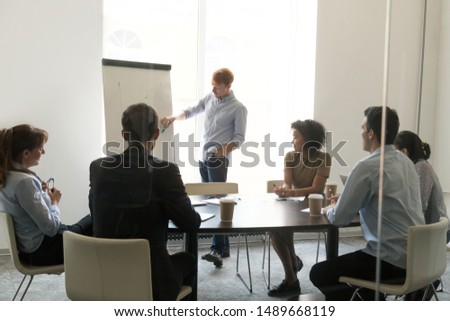 Millennial male coach or trainer make flipchart presentation for multiracial work group in office, man speaker or presenter draw discuss project with diverse colleagues at briefing in conference room