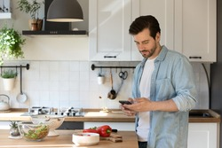 Millennial male distracted from preparing food hold smartphone order missing ingredients online. Young man husband stand at modern kitchen using cell consulting with wife about cooking process details
