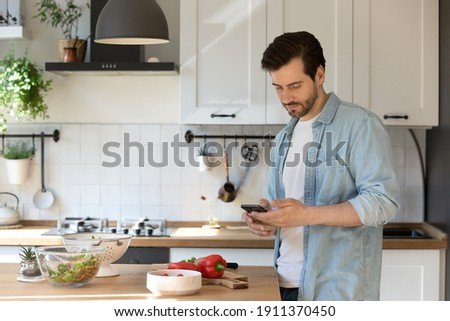 Millennial male distracted from preparing food hold smartphone order missing ingredients online. Young man husband stand at modern kitchen using cell consulting with wife about cooking process details Stock foto ©