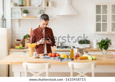Millennial man preparing romantic dinner on home kitchen. Serious concentrated guy looking for good recipe at smart phone. Healthy food menu app. Cookbook mobile application. Technology and home