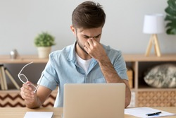Millennial man sitting at the desk in office at workplace took off glasses massaging his eyes. Fatigue and stressful work, poor blurred vision influence of laptop on human health, overworking concept