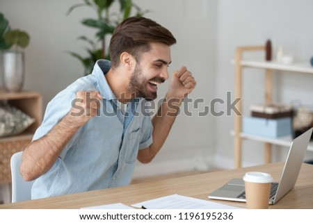 Millennial man sitting at the desk looking at computer device screen celebrating win feels happy received a great news, took on a good post hired or employee getting reward, successful deal concept