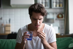 Millennial man taking antibiotic antidepressant painkiller pill medication to relieve pain at home, young guy feeling sick ill suffering from headache, stress or flu, emergency treatment concept