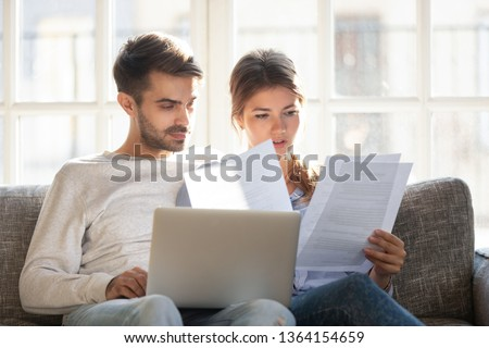 Millennial married couple sitting on couch with computer and documents, reading received formal letter from bank loan mortgage information, contract terms and conditions discuss papers working concept