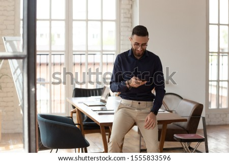 Millennial middle eastern ethnicity businessman with smartphone in modern office room, before start briefing entrepreneur uses gadget standing alone check mail having formal or informal chat concept
