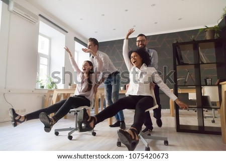 Millennial multiracial team people having fun riding on chairs in office room, excited diverse employees laughing enjoying funny activity at work break, creative friendly workers play game together