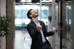Millennial office worker in suit standing in hallway clenched fists feel overjoyed celebrate career advancement, got business opportunity, salary or sales growth, successful winner businessman concept
