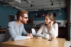 Millennial red-haired man approaching beautiful young girl enjoying coffee and dessert in café, interested young guy get acquainted with pretty female, young people flirt sitting in coffeeshop