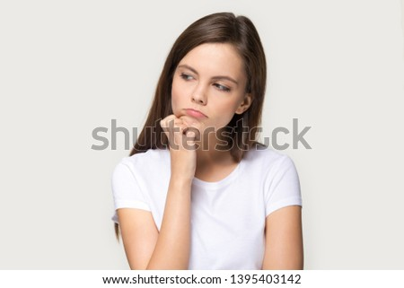 Millennial sad pensive female touches chin looking away feels upset isolated on grey background, disappointed offended girl in white t-shirt pouting lips is bored having problem difficulties concept