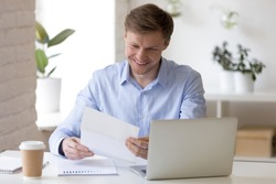 Millennial satisfied businessman sitting at the desk in office room holding paper document reading letter feels happy excited by great news. Employee getting salary raise or bonus from company boss