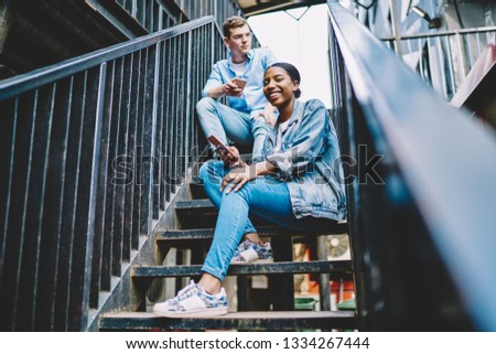 Millennial smiling 25 years old friends using smartphones enjoying generation z lifestyle sitting outdoors on stairs. Casual dressed diverse hipster guys with mobile phones. Using modern technologies