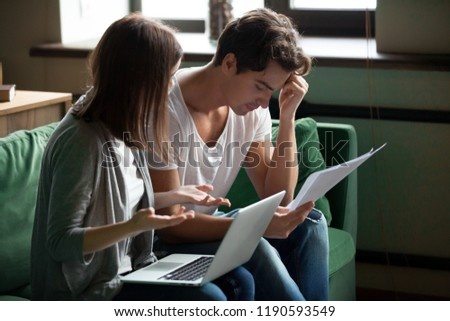 Millennial stressed young couple sitting on sofa at home and checking unpaid bills, taxes, due debt, bank account balance. Bankruptcy, debt and lack of money, financial problems in family concept