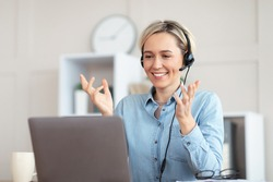 Millennial teacher giving online lesson on webcam from home, blogger broadcasting on air. Young tutor in headphones participating in educational or business web conference on laptop