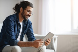 Millennial Western Guy Spending Time With Digital Tablet At Home, Reading News, Browsing Internet, Watching Videos, Checking Social Networks While Relaxing On Couch In Living Room, Copy Space