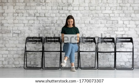 Millennial woman sit on chair in office corridor do remote work communicates with customers via email. Student learn study using laptop, browse information while waiting appointment in office concept