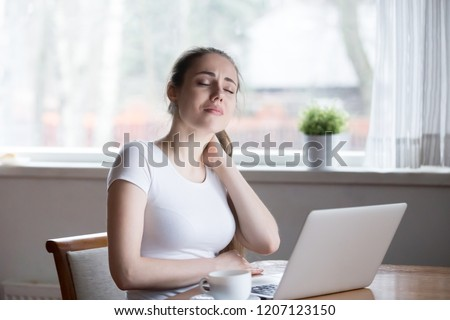 Millennial woman sitting in kitchen at table touch massage neck. Exhausted tired girl suffering from neck pain ache after sedentary work or study at home for a long time feeling unwell and discomfort