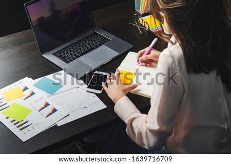 Millennial woman working on laptop. Manager sitting at office desk and performing project using corporate software on PC. Career opportunities for young specialist, enterprise practice, education