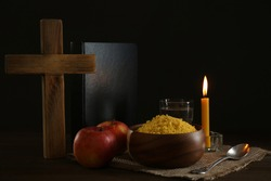Millet, apple, water, burning candle, Bible and cross on wooden table. Great Lent season