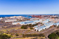 Mills, warehouses and storage yards of Port Kembla industrial site and sea port near Wollongong in Australia. Elevated aerial view across site towards open sea on a sunny day.