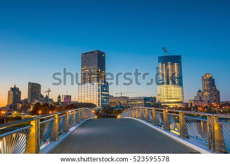 Milwaukee skyline at twilight with city reflection in lake Michigan and harbor pier. #523595578