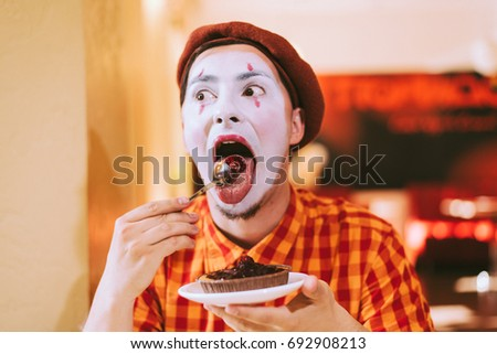 Mime eats cake in a cafe and croaks a face #692908213
