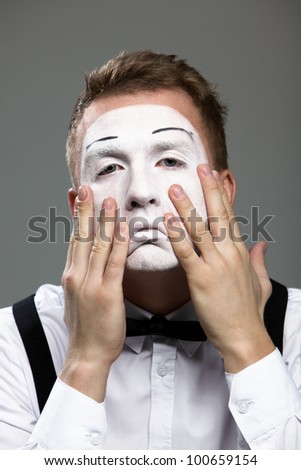 Mime face and hands in a theatrical make-up isolated on gray background
