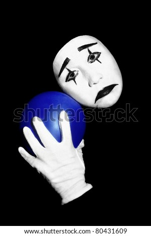Mime with blue balloon in the white hand isolated on black background.