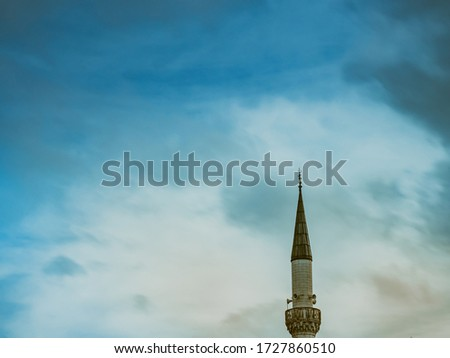 Minaret of a Muslim mosque on the background of the cloudy sky. minaret aspiring to heaven.