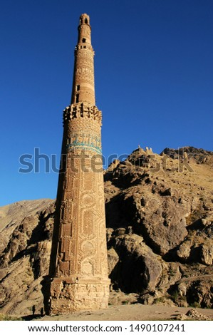 Minaret of Jam, Ghor Province in Afghanistan. The Jam minaret is a UNESCO site in a remote part of Central Afghanistan. Two silhouettes of people at the base of the Minaret of Jam indicate the scale.