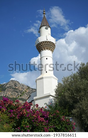 Minaret of Yeni Mosque (Cami in Turkish) Kas, Turkey. The stone ornaments at the entrance date back to 1881, when it was a Greek Orthodox church. The Yeni is uphill from Kaş' main square. Stok fotoğraf ©