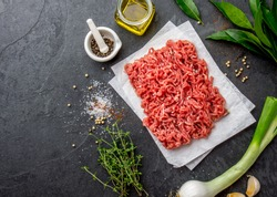 Mince. Ground meat with ingredients for cooking on black background. Minced beef meat. Top view.