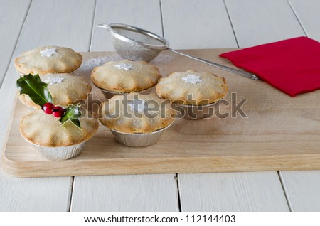 Mince pies on a wooden board, decorated with star shapes and holly.  A red napkin, old tea strainer (sieve) and scattered icing sugar rest on the board which sits on a white, planked table.