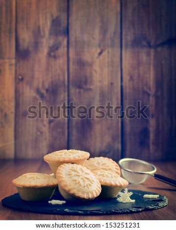 Mince pies on slate serving plate in rustic vintage setting