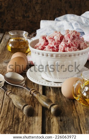 minced meat in a bowl and different ingredients on an old wooden table.meat dishes