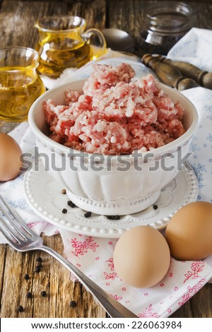 minced meat in a bowl and different ingredients on an old wooden table. meat dishes