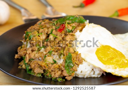Minced pork basil in black plate on wood table, space for text input. (Select a specific focus) #1292525587