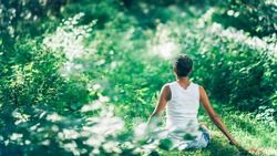 Mind calming inner peace outdoor meditation. An unrecognizable mindful woman meditating surrounded by lush, green vegetation, increasing her calmness and inner peace