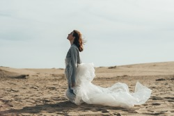 Mind freedom. Inner peace. Soul recreation. Meditation enlightenment. Profile art portrait of calm woman with polyethylene film standing on knees enjoying wind energy in sand desert with cloud sky.