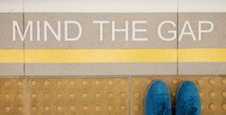 Mind the gap sign painted on train station's platform edge, top view with man's feet or shoes, focus on the warning text