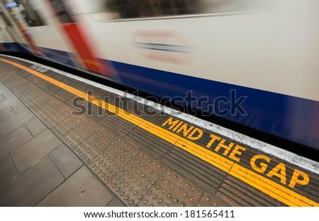 Mind the gap sign with speeding train in London underground. #181565411