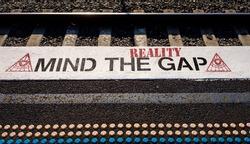 Mind the reality gap, graffiti on station platform, all seeing eye image, conspiracy theory, Illuminati, secret society, QAnon, G5, flat earth cults. Concept illustration