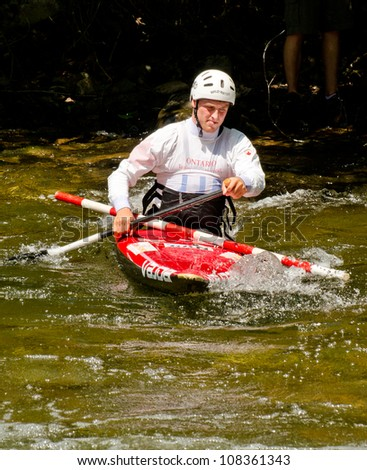 MINDEN, ONTARIO - JULY 21: An unidentified kayaker transports a replacement slalom gate pole at Ontario Summer Race 2012 on July 21, 2012 at Gull River in Minden, Ontario, Canada.