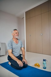 Mindful aging man kneeling on a yoga mat with his hands of his knees while having his eyes closed