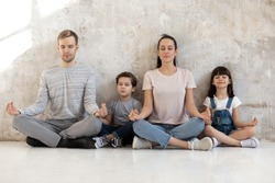 Mindful calm happy fit family of young parents and little kids sitting together on heated warm wooden floor in lotus positions, meditation, practicing breathing yoga exercises. Wellness hobby concept