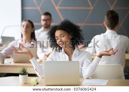 Mindful millennial african woman meditating at workplace with colleagues, calm black employee or student doing yoga exercises feeling zen enjoying no stress free relief, corporate meditation concept